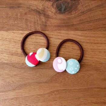 「カバードボタン」という市販のボタンで、手作りのくるみボタンができます。作り方は布を台座に入れ込み、上からぎゅっと押すだけ。ヘアゴムを付ければ髪飾りになります。好きな色や模様の髪飾りは、きっとお子さんのお気に入りになりますよ♪