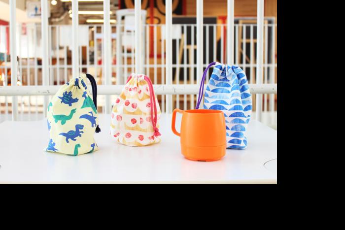 入園グッズの一つであるコップ袋も、ハギレで作れちゃいますよ。2つのパーツを縫い合わせた後、布をジグザグに折り畳んで縫い、最後に紐通し部分を作って完成です。コップがすっぽり入るちょうど良い大きさです。