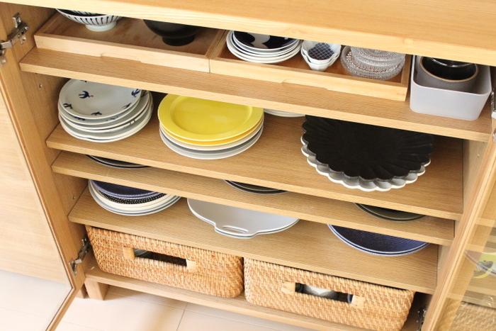 食器棚はお気に入りのレギュラーたちをメインに収納、普段出番の少ない食器はかごにまとめてしまえばスッキリ!お茶碗や豆皿など小さい食器をトレイに乗せて引き出せるようにするアイデアは、奥行まで無駄なく収納できますね。