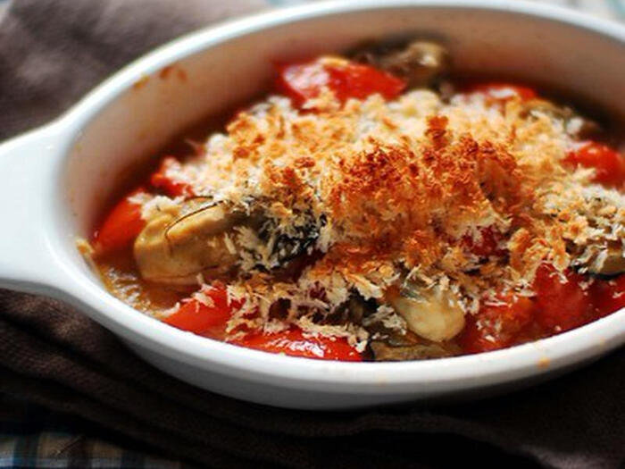 """牡蠣、ミニトマトはにんにくと白ワインでさっと蒸し煮にしてオーブンへ(煮過ぎに注意:牡蠣が縮んでしまいます)、とこちらも""""ワンパン""""系。 「煮込むときにパン粉を少し入れておくと、とろみのついたスープになって美味しいのです」と作成した遠藤文香さん、「牡蠣とトマトのうまみが出たスープは、バゲットにひたして食べるととっても美味しい!」。"""