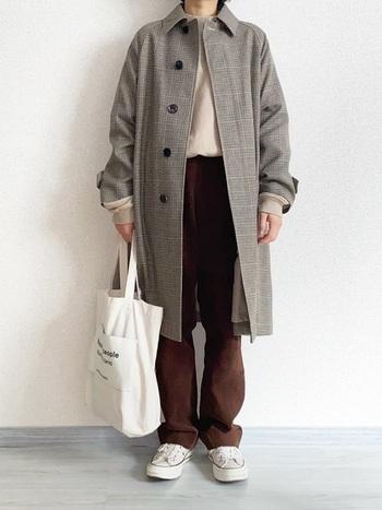 ブラウンのコーデュロイパンツに、ステンカラーコートを羽織ってきれいめにまとめたコーディネート。ブラウンとベージュの色合いが冬にぴったりです。