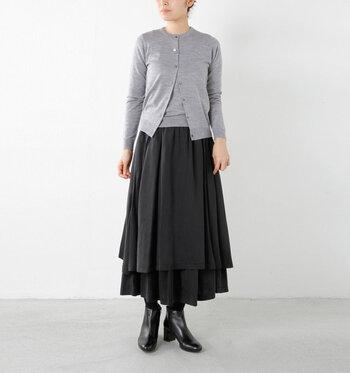 グレーのアンサンブルニット×黒のティアードスカートの大人シンプルコーデ。重なった裾のボリューム感をシャープなフォルムのショートブーツが引き締めています。