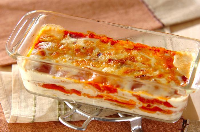 玉ネギとベーコンを炒めたら、生クリームを加えて1分ほど煮て塩コショウで味を調え、耐熱皿にスライス餅と交互に敷いてオーブンへ。しゃぶしゃぶ用のスライス餅にからむ生クリームとミートソース(市販)、ベーコンのコクが真冬の食卓に◎。