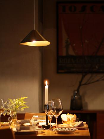 無駄のないシンプルなフォルムが美しいシェード、優しい光が魅力のペンダントライトを食卓に。キャンドルの光と混ざり合って、幻想的な空間を演出しています。