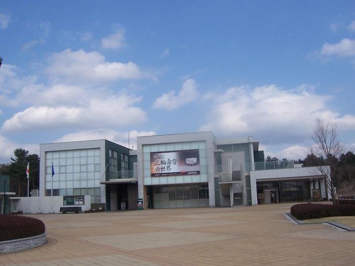 """「笠間工芸の丘」の東側正面に位置するのが、「茨城県陶芸美術館」。""""伝統工芸と新しい造形美術""""をテーマにした、東日本で初めての陶芸専門の公立の美術館です。  近代陶芸の祖・板谷波山」や人間国宝・松井康成の作品などが常設展示される他、日本を代表する名だたる陶芸家らの作品が並び、陶芸好きなら一度は足を運びたい美術館です。ミュージアムショップでは、笠間焼やグッズも購入できます。"""