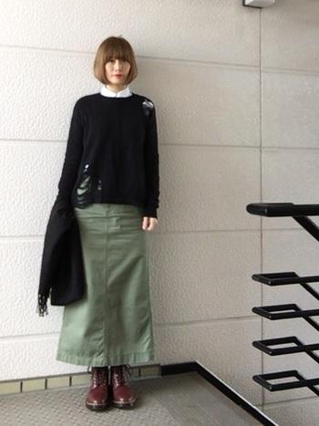 カーキのロングスカートにドクターマーチンのワークテイストのブーツがマッチ。トップスは白シャツとジャストサイズの黒セーターを合わせることで、上品に仕上げています。