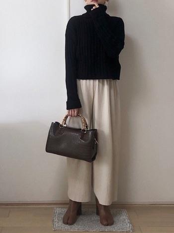 ブラックのタートルニットには、明るいカラーのリブパンツとブラウンの足袋ブーツでやわらかい印象に。バッグにはよりダークなブラウンを入れることで全体のカラーバランスを支え、より洗練された印象に仕上がります。