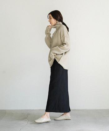 ベージュのゆるタートルネックに、黒のスカートを合わせたシンプルなコーディネートです。足元はトップスとカラーを合わせて、全体をベーシックにまとめています。ゆるトップス×タイトスカートの組み合わせが、絶妙なバランス感ですね。