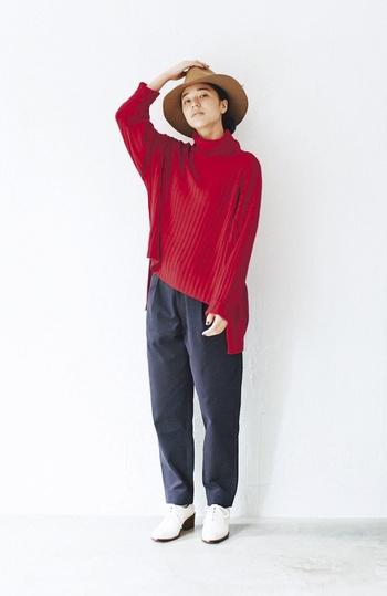 赤のゆるタートルネックに、ネイビーのパンツを合わせた着こなし。ツバが大きめのハットをかぶって、レディライクな印象のスタイリングです。足元は白のシューズで、爽やかさをさりげなくプラス。