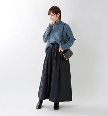 ブルーのゆるタートルネックニットを、黒のロングスカートに合わせた着こなしです。ブーツやバッグも黒で揃えて、トップスが主役になるようなコーディネートに仕上げています。