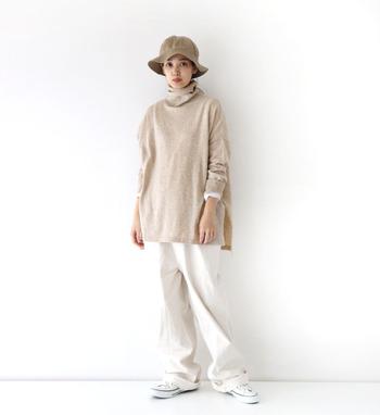 ベージュのタートルネックトップスに、白のワイドパンツとシューズを合わせた着こなしです。トップスの袖からさりげなく覗く白インナーが、ほどよいアクセントと統一感を与えています。ハットでこなれ感を演出して、ラフになり過ぎないコーディネートに。