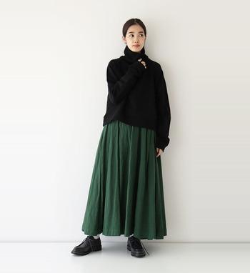 黒のゆるタートルネックに、深みのあるグリーンのフレアスカートを合わせた着こなしです。足元は黒のシューズで、全体をダークトーンでまとめています。アウターはショート丈をチョイスして、スカートが隠れないようなスタイリングがおすすめです。