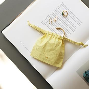 紙製のように見える、ユニークなデザインのミニポーチ。耐久性があり、水濡れにも強い素材を使用しているので、水が掛かっても問題ありません。パッと目を引く明るいイエローは、バッグの中にあるだけで気分をグッと上げてくれそうですね。