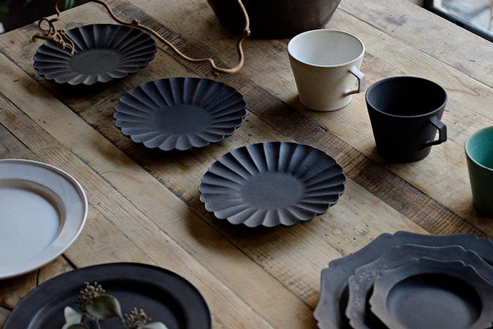 金属のような、陶器のような、石のような。独特の質感が魅力のカタチ製作所のプレート。長野の陶芸家・佐々木一樹さんが手がける陶器は、名前の通り、形や陰影の違いでいろいろな表情を見せてくれます。例えば花のようなリムのプレートは、黒なのに重たさはなく、どこか華やか。