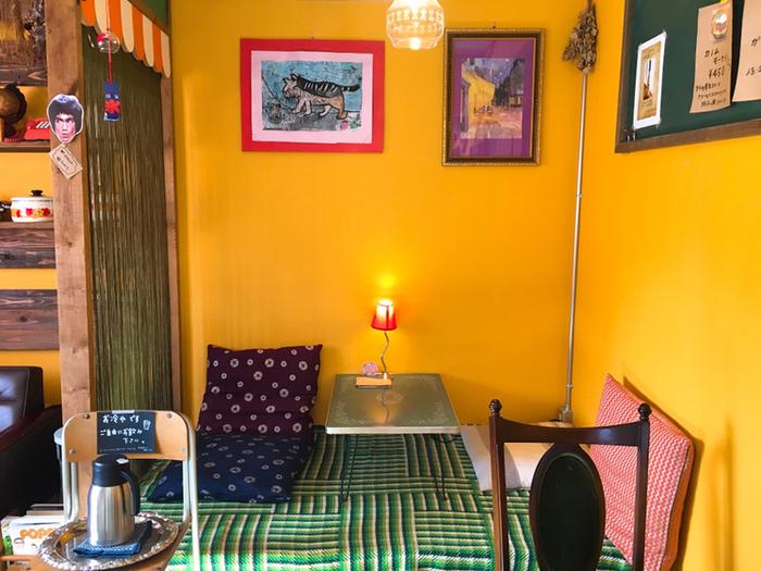 黄色い壁やその壁に飾られたアートが印象的な席。座椅子なので、足をのばしてまったりとくつろげますよ。
