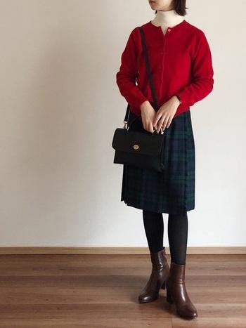 赤のカーディガンと白のハイネックのコントラストが美しい組み合わせ◎ クルーネックから除くハイネックは、よりクラシカルな雰囲気。落ち着いたチェック柄のスカートがよく映えた、まとまり感のあるスタイルです。