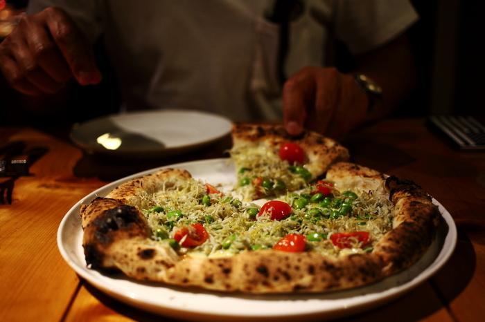 東慶寺の門前、古民家を改築したトラットリア「タケルクインディチ」は、ナポリピザとイタリアンが評判の北鎌倉の人気店です。画像は「そら豆と釜揚げシラスのピザ」。本場イタリアから取り寄せたという薪窯で焼いた生地はモチモチの美味しさだそう。