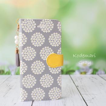 グレーの背景に白い小花がデザインされた、上品なケースです。ベルト部分の黄色がアクセントになっていますね。