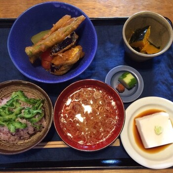 【8月のごはん】 夏野菜をたっぷり使ったこの年の8月のメニュー。冬瓜とトマトの冷菜に、オクラとナスの天ぷらが添えられています。「胡麻豆腐」は、年間を通して提供される人気メニューです。
