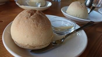 【自家製パン】 ランチに付いてくる自家製のパン。酵母の風味を楽しめる素朴な丸パンには、バターが添えられています。