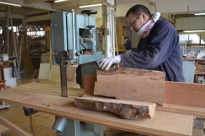男性3⼈でやっと持てるほど重い幹を⼯場に運び、さらにチェーンソーで割る。その後専用のマシンで製材作業をおこなう。リンゴの木はとても固いため、細心の注意が必要(写真:木村木品製作所)
