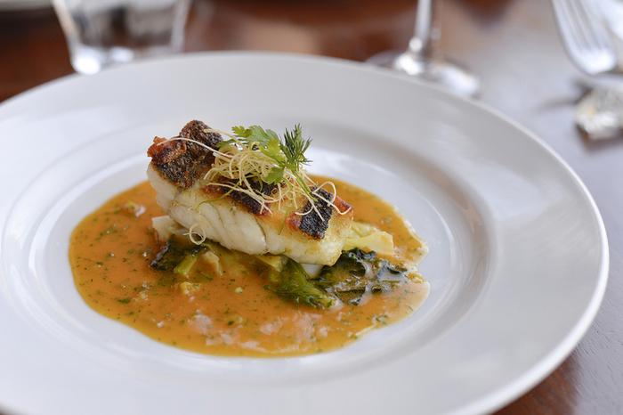 画像は、皮はパリッと中はふっくら焼き上がったメインの魚料理「スズキのソテー、蕗の薹のソース」。「ラ・ペクニコヴァ」には素材の旨味をシンプルに活かしながら巧みなソース使いで仕上げる、一口一口丁寧に味わいたい料理が並びます。