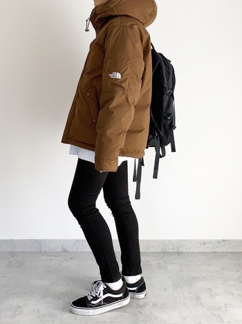 黒のパンツや小物で統一したシンプルコーデに、ライトブラウンのダウンジャケットを合わせたスタイル。所々で白を加えることで効果的に明るさを加えています。