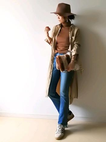 ライトブラウンのタートルニット×デニムに、ベージュのシャツワンピースを羽織ったコーデ。ブラウンとベージュの組み合わせで、よりナチュラルで優しい印象に。帽子やバッグもブラウンを取り入れて統一感を持たせています。