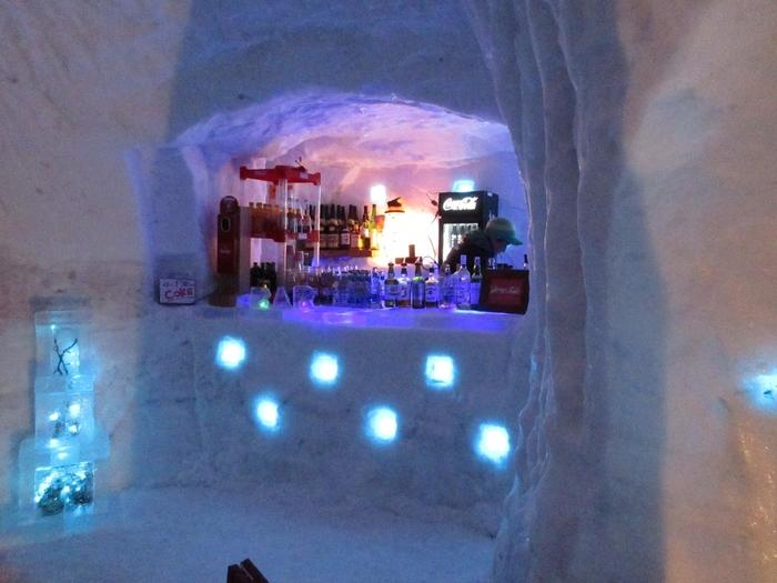 """旅籠の中には、冷えたからだに嬉しいホットワインなどお酒がのめる「アイスバー」や、地元の和菓子が食べられるお店など、様々なグルメを楽しめるスペースも◎。椅子やテーブルまで雪と氷でできており、非日常で美しい""""冬の世界""""が広がります。"""