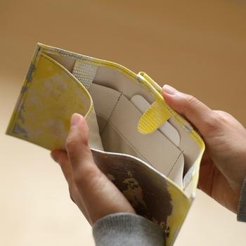 大きく開く硬貨を入れるポケットと、お札を入れる三つ折りのスペースに分かれています。カードを入れるポケットの上には滑り出し防止の工夫も。