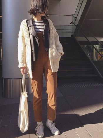サロペットにレザージャケット、ニットカーディガンと、異素材のアイテムを重ねた上級者スタイル。 おしゃれに見えるうえ防寒性もあるので、コートの着こなしに飽きてしまったときにも◎