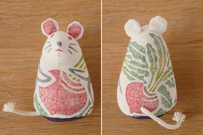 やさしい色使いで彩りある木版手染は、左右対称の模様を一つの版木に深く彫り、布の伸縮でズレないように、一度にすべての色をのせて刷られています。そして、高温で蒸して色を定着させた後、一針一針手で縫い合わせて制作しています。