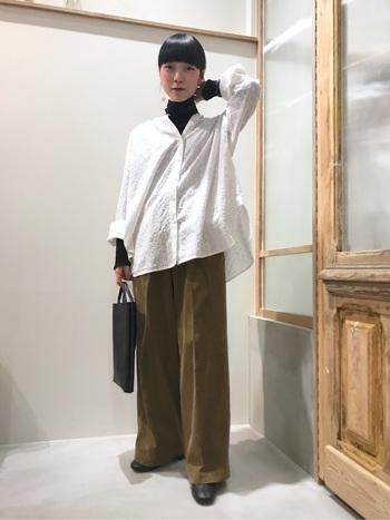 白のゆったりシャツから、黒のハイネックトップスをチラ見せしたスタイリング。袖もロールアップして、インナーの黒をさりげなく見せているのがポイントです。ボトムスはワイドパンツで、ゆったりラフな印象に。