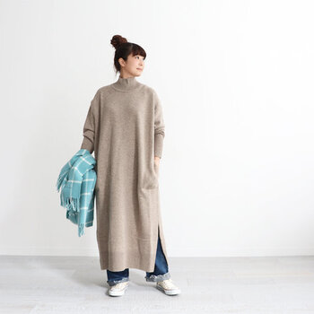 マキシ丈のニットワンピースは深めのスリットで重ね着も楽しめそう。ゆったりとした身の作りや、袖の長めのリブがおしゃれです。