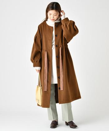 ウェストをシャーリングして縛れるコート。リボンがとっても印象的。女性らしいシルエットなのでインナーはシンプルに。