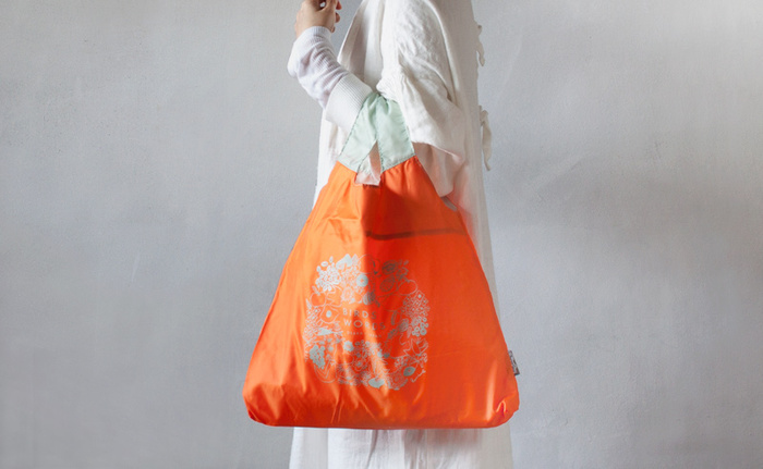 ビビットなオレンジ色が可愛いマルシェバッグ。野菜や果物などのデザインもおしゃれですね♪収納袋がバッグにくっついていて、畳んで入れると巾着のような形に収まります。