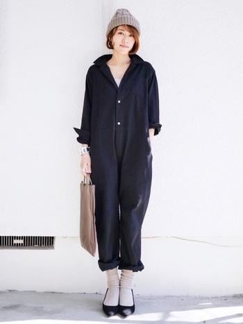 黒のオールインワンに、明るいベージュのニット帽をプラス。靴下やバッグなど小物と色を統一し、落ち着きがありながらも柔らかなニュアンスのあるスタイルに。