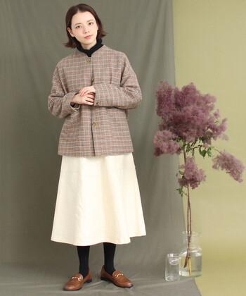 上品でクラシカルな印象のガンクラブチェック柄のショート丈コートは、白のフレアスカートを合わせて日常使いのコーデに。やさしい着こなしになっているのは、足元を茶色の革靴がポイントです。