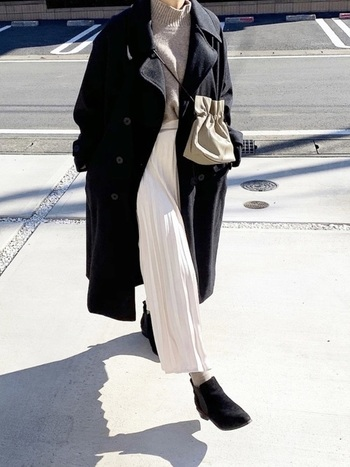黒のロングコートから見える白のプリーツスカートが冬コーデに軽さをプラスしてくれます。動くたびに揺れる白のプリーツスカートは華やかな印象。冬のお出かけや旅行シーンにもおすすめのコーデです。