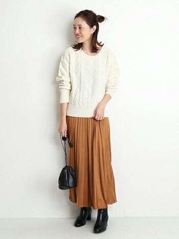 白のケーブルニットにキャメルブラウンのプリーツスカートを合わせた明るい印象のコーディネート。バッグとブーツを黒で統一して程よく引き締めています。