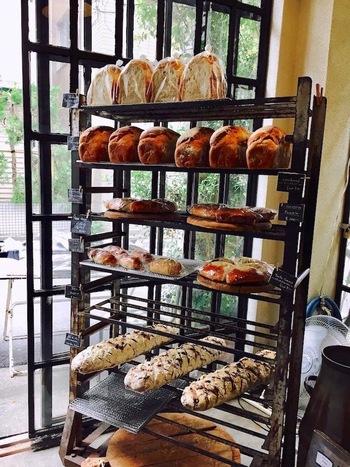 """1階は入り口近くにパン屋さんと厨房、奥まってショップが。 """"ヨーロッパの田舎暮らし""""が店のテーマだけに、パンのラインナップはカンパーニュなどハード系が中心ですが、柔らかなクリームパンやシナモンロールもあります。"""