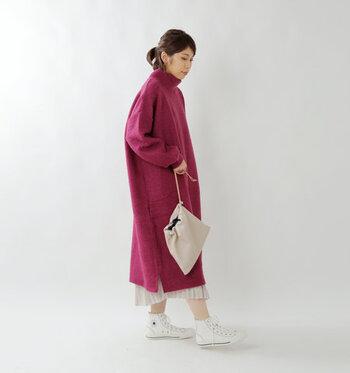 マゼンタカラーのニットワンピースに、白のプリーツスカートを合わせたコーディネートです。スニーカーもスカートと色を合わせ、統一感のある着こなしに。肌色を見せてカジュアルにまとめているのもおしゃれ見えポイント。もっと大人っぽくしたい時は、タイツ×パンプス or ブーツでフェミニンに仕上げても◎。