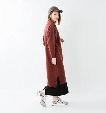 ブラウン系カラーのニットワンピースに、黒のベーシックなスカートを重ねたコーディネートです。ワンピース×キャップ×スニーカーのカジュアルコーデに、黒のスカートで大人っぽさをプラスしているのがポイント♪