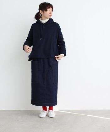 ネイビーのデニムタイトスカートに、同系色のパーカーを合わせたカジュアルコーデ。襟元から白のハイネックを覗かせて、今っぽさをしっかり演出しています。足元は白スニーカーで爽やかにまとめつつ、赤ソックスでアクセントをプラス。