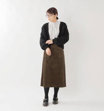 ブラウンのコーデュロイタイトスカートに、ブラウスと黒カーディガンを合わせた着こなし。黒タイツで上品にスタイリングすれば、オフィスカジュアルとしても使えるコーディネートの完成です。