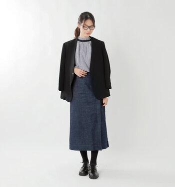 ネイビーのタイトスカートに、ブラウスとジャケットを合わせてキレイめに仕上げたスタイリングです。黒タイツと黒シューズで上品にまとめて、カジュアルな印象のスカートをちょっぴりクラシカルに着こなしています。