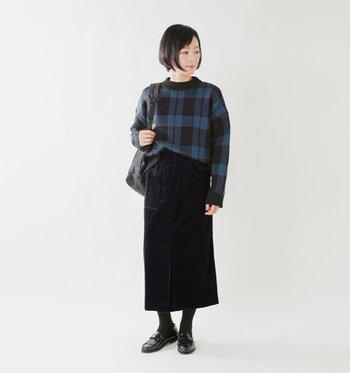 コーデュロイ素材の黒タイトスカートに、チェック柄のトップスをゆるくタックインした着こなしです。タイツやシューズも黒で揃えて、全体をダークトーンに。シックな大人コーデの完成です。