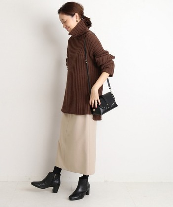 ベージュのロング丈タイトスカートに、ブラウンのロング丈タートルネックを合わせたコーディネートです。足元はタイツとショートブーツで、季節感のある大人コーデに。コートやジャケットなど、どんなアウターとも合わせやすいスタイリングです。