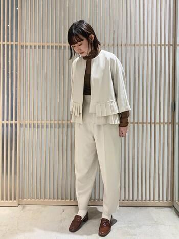 爽やかなイメージの白のセットアップも、こっくりとしたブラウンをインナーや足元に取り入れることで、どこかあたたかな印象に。ジャケットのプリーツデザインがほんのり個性を加え、透け感のあるインナーもバランスよく馴染んでいます。