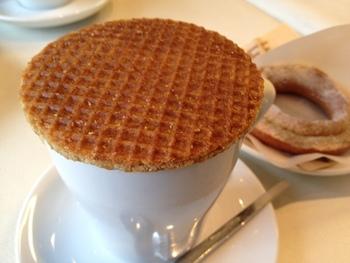ストロープワッフルとは、かために焼かれた二枚のワッフル(クッキー)の間にキャラメルシロップを挟んだ、オランダのお菓子です。オランダの人達は、このワッフルを紅茶やコーヒーのカップの上に蓋をするように乗せ、温めて食べます。温めることで中のキャラメルが溶け、柔らかいワッフルに。